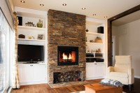 Salon avec foyer au revêtement de pierre et meubles built-in de chaque côté
