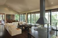 Salon aire ouverte avec foyer 4 faces et fenestration du plancher au plafond